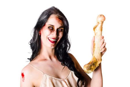 fractured: Halloween female zombie laughing and holding fractured  human bone isolated on white background