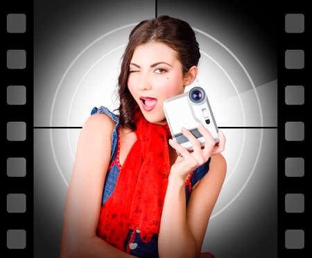 cinta pelicula: Mujer hermosa que sostiene la cámara de vídeo doméstico en el fondo de película de época