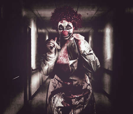 Madness the creepy medical clown standing in grunge hospital hallway with flashlight and tongue prong. Terminal treatment Stock Photo