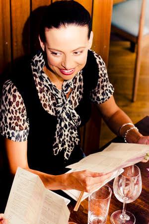 animal print: Mujer sonriente sentado en una mesa de restaurante con su pareja mirando a través de las ofertas de menú de la cena Foto de archivo