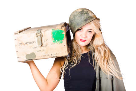 buxom: Beauty portrait of a reinforcements pinup girl wearing army helmet holding weapon supplies crate in a depiction of militia backup Stock Photo