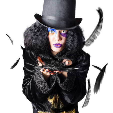 black magic: Beautiful woman magician with black top hat and colorful blue and purple makeup blowing a handful of birds feathers