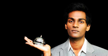 summon: Asian hotel Bellboy holding bell on black background
