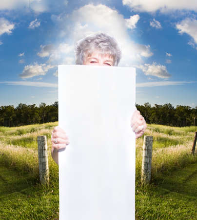 blank sign: Mature Woman With Gray Or Grey Hair Looking Over Blank White Sign In Countryside With Blue Sky And Cloudscape Background