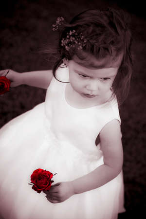 flowergirl: A Cute Toddler Wearing A White Dress Holds Red Roses With An Adorable Stubborn Expression On Her Face, Black And White With Red Accent Color