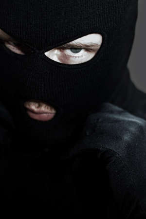 conman: Headshot Of A Thief Putting On His Balaclava During A Twilight Robbery