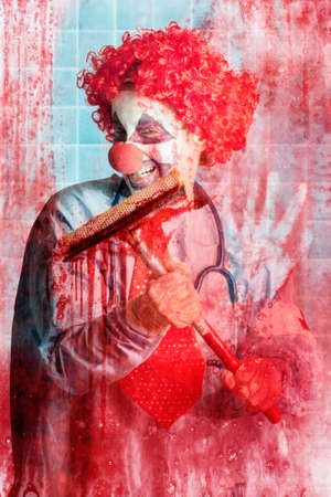 clownophobia: Scary hospital clown cleaning blood smeared window pane in hospital surgical ward. Stock Photo