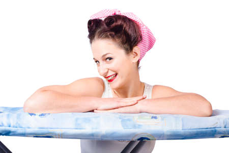 ironing board: Adorable sixties pin up lady resting on ironing board wearing headscarf and old-fashioned hair style. On white background Stock Photo