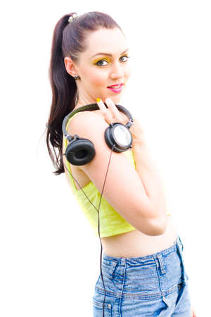 head phones: Isolated Studio Portrait Of A Beautiful Young Brunette Girl Holding A Set Of Earphones Or Head Phones Standing In A Cool 80s Fashion Sound Portrait, White Background