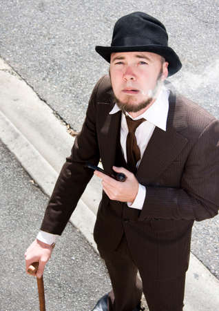 stood up: High Angle View Of Old Fashioned Gentleman In Suit With Walking Cane And Bowler Hat Smoking Pipe On The Hazy Streets Of Yesterday