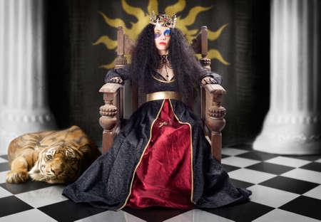 edad media: reina de alta moda con estilo morena de pelo ondulado y maquillaje creativo que se sienta en el trono con la corona de oro y un vestido medieval en la sala de espera del bufón