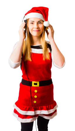 holiday music: Attractive young girl listening to holiday music with headphones in santa costume. Sounds of festivity Stock Photo