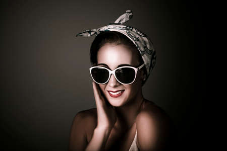 sunnies: Dark Studio Fashion Portrait Of A Charming Retro Pin Up Woman Wearing Sunglasses And Head Scarf On Copy Space Background