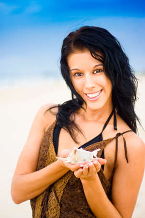 top animated: Beautiful Beach Woman With Black Hair Smiling With Happy Expression And Holding A Seashell As If She Is Enjoying Her Day At The Beach Against Blue Sky Summer Background