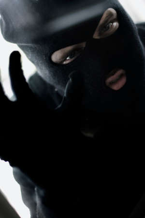 intrude: Photograph Of A Robber Looking Through A Glass Window With A Look Of Intent To Intrude Stock Photo