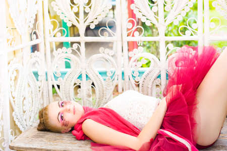 mini: Caucasian Female Ballerina Doll In Beautiful Cosmetics Lays Down On A Wooden Bench Wearing A Cherry Colored Tutu In A Fresh Portrait Titled Sleeping Beauty