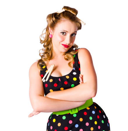 hairclip: Happy young housewife with curlers in hair and clothes pins on polka dot dress, white background Stock Photo