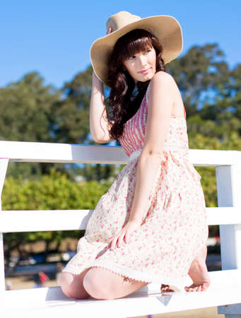 holidaying: Woman Rests Her Knees On A Pier Bench While Modeling Her New Summer Hat Stock Photo