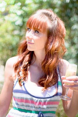 arboles frondosos: Retrato de medio cuerpo atractivo de la mujer joven con el pelo casta�o y copa de cava frondoso �rboles en el fondo Foto de archivo