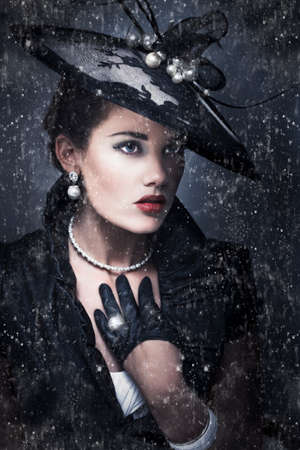 sombre: Dark sombre portrait of a beautiful woman widow dressed in a haute couture black outfit standing outside in the pouring rain during a funeral service Stock Photo