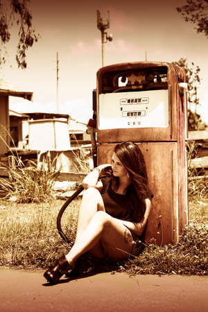 depletion: A Woman Sits By A Petrol Pump In The Ghost Town Named Oil And Gas Waiting For A Environmentally Friendly Viable Alternative In A Energy And Environment Concept