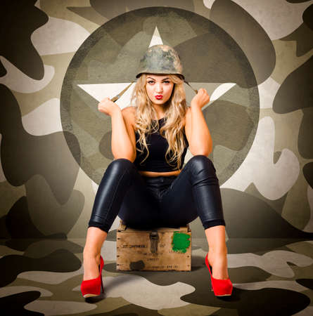 army girl: Beautiful blonde army pinup woman sitting on military ammunition crate wearing helmet and red heels. Fashion recruit
