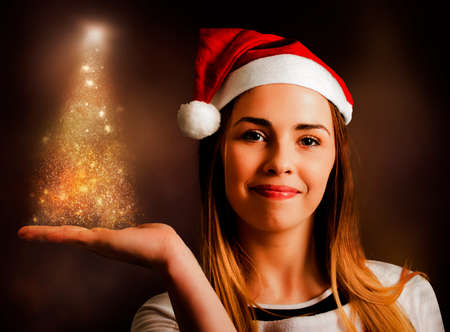 christmas display: Magic holiday art of a beautiful woman in santa hat displaying christmas tree lights with hand copy space. Xmas decoration girl Stock Photo
