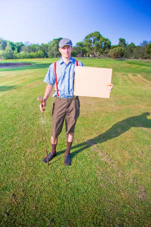 flat cap: Golf Player Wearing Vintage Flat Cap Makes A Statement While Holding A Sign On A Green Grass Sports Fairway