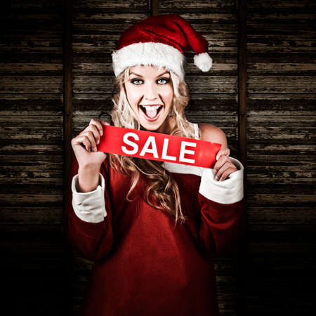 christmas woman: Excited Christmas Woman With Happy Expression Holding Sale Advertising In A Depiction Of A Xmas Discount Shopping