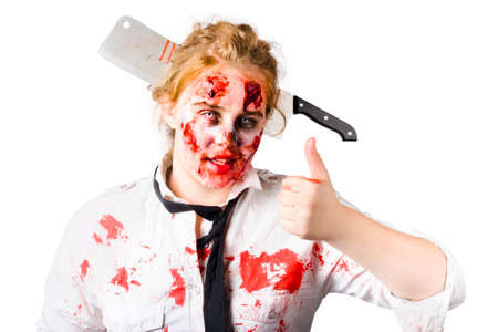 horrific: Bloody and beaten woman with large meat cleaver in her head, gesturing thumbs up. Zombie apocalypse survivor Stock Photo