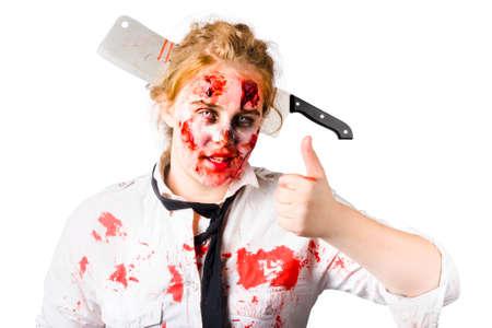 mujer golpeada: Mujer sangrienta y golpeada con un gran cuchillo de carnicero en la cabeza, haciendo un gesto pulgar hacia arriba. Zombie sobreviviente apocalipsis Foto de archivo