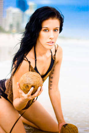 kneeling woman: Attractive Young Woman With Black Hair Kneeling In The Sand With Questioning Expression Stock Photo