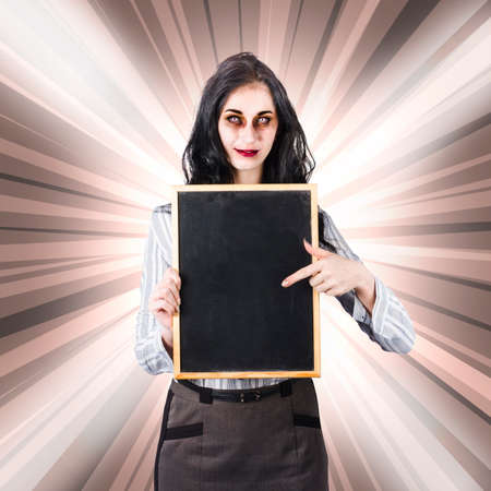demoniacal: Female model roleplaying a sinister school teacher character wearing demoness makeup with halloween copyspace chalkboard