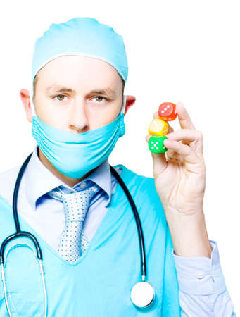 probability: Surgeon in mask and gown holding up a set of three colourful dice in a surgery risk, probability and chance, or dicing with death concept