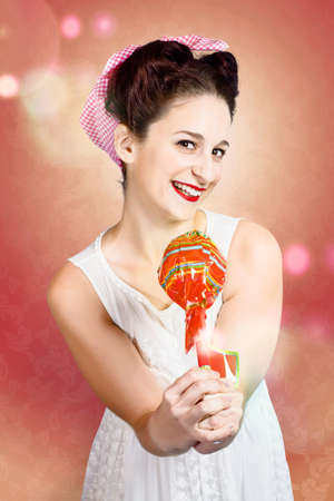 confectionary: Sweet as sugar lollipop pinup woman offering wrapped up treat with retro 60s updo hairstyle. Confectionary store girl