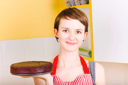 chocolate treats: Portrait of a satisfied smiling woman wearing apron holding a easter chocolate cake when baking tasty treats Stock Photo