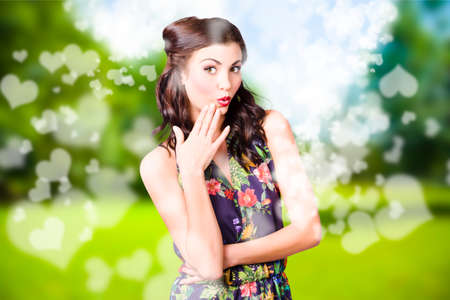 niñas sonriendo: Beautiful valentines day woman with perfect hair and makeup, showing adorable surprise expression in bright green field of abstract heart shapes. Cosmetic love Foto de archivo