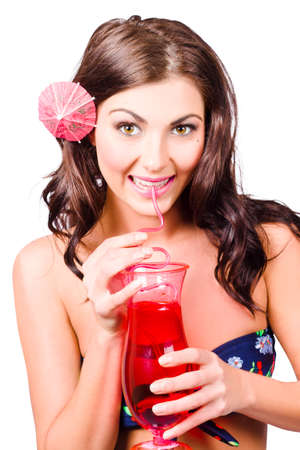 cocktail bar: Smiling tropical girl drinking red cocktail drink during summer holidays. Sweet holiday treat