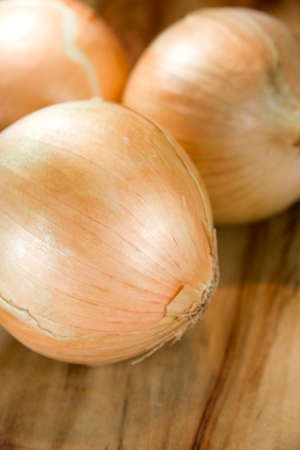 edibles: Onions Placed On A Wooden Kitchen Chopping Block