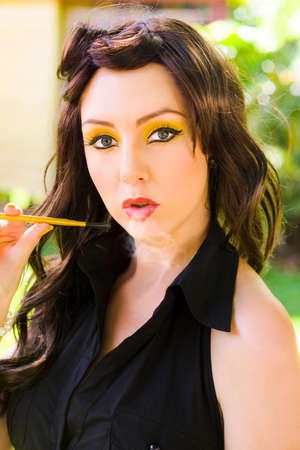 inhaling: Smoker Woman Wearing Bright Yellow Makeup Cosmetics Blows A Puff Of Smoke Out Of Her Mouth While Inhaling And Exhaling Toxic Fumes In A Smoking Addict Concept
