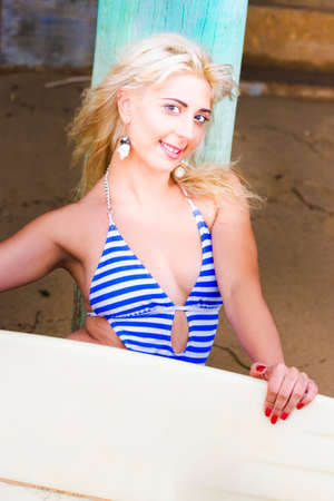 togs: Happy Smiling Athletic Blonde Woman In Her Twenties Sits In Blue Striped Swimming Togs At A Beach Bridge Pillar Holding Surfboard In A Fit And Active Concept