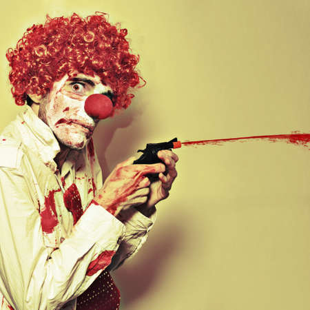 Disturbed Manic Clown In A Bloodstained Costume With A Depraved Look Shooting Blood From A Small Waterpistol Or Popgun In A Halloween Horror Concept