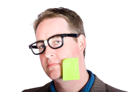 reminding: Absent minded male marketing manager seeking inspiration with blank page memo stuck to head over white