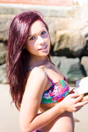 auburn: Closuep Half Body Portrait Of A Wistful Girl In Bikini Reading A Book Of Romance Stories While Dreaming Away On A Coast Shoreline During A Dreamy Holiday Stock Photo