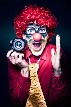 clown birthday: Excited Young Male Photographer Clown Holding Camera While Shouting Out Cheese At A Kids Birthday Party Celebration On Dark Studio Background