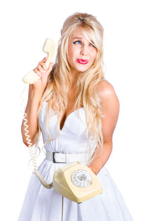teary: Sad blond woman in white dress with retro telephone, studio background Stock Photo