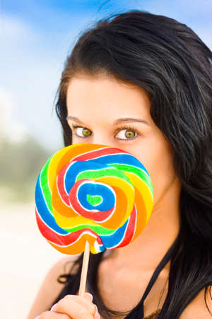 mesmerising: Beautiful Young Female With Vibrant Hazel Eyes Poses With Colorful Candy And An Expression Of Love And Passion For Lollipops Against An Outdoor Background Stock Photo