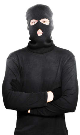 concealing: Young thug turned criminal posing with his arms folded wearing a black outfit with hooded mask to conceal his identitiy, isolated on a white studio background Stock Photo