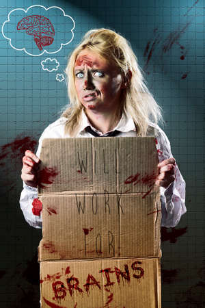 fine art portrait: Halloween fine art portrait of an unemployed business zombie standing at underground subway holding cardboard sign WILL WORK FOR BRAINS. Funny horror poster artwork Stock Photo