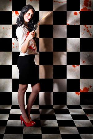malevolent: Horrible zombie girl holding pruning saw when slicing and dicing in a game of horror, black and white chequered background Stock Photo